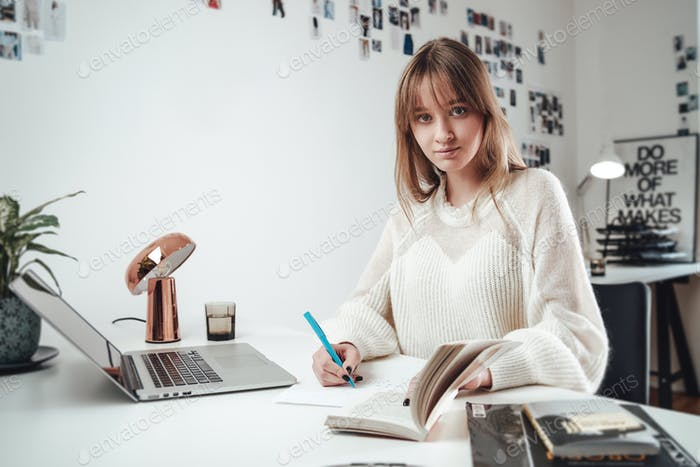 Cheerful caucasian woman works on laptop writing on paper in office