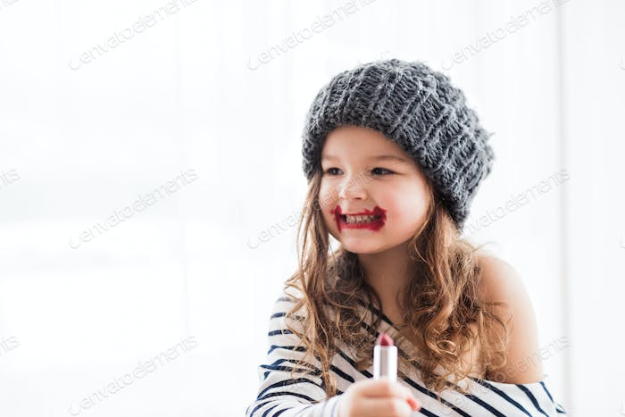 A small happy girl in striped T-shirt at home applying a lipstick.