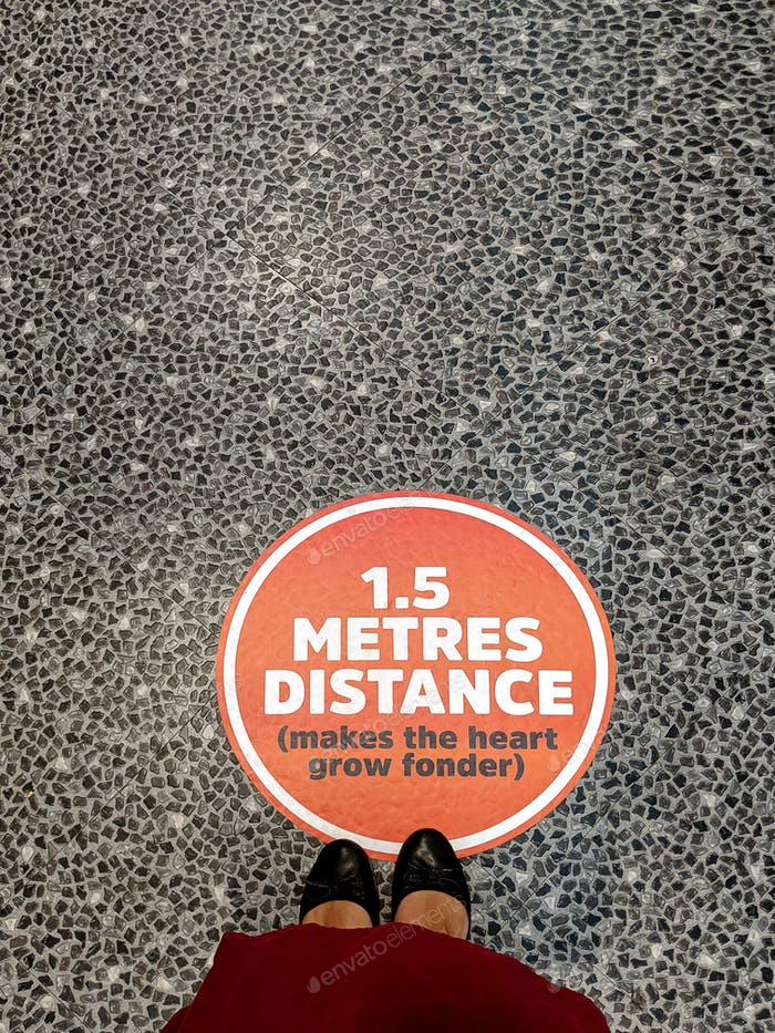 Woman's feet next to 1.5m distance sticker fixed over the floor