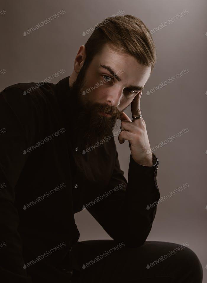 Sepia Fotoporträt eines nachdenklichen Mannes mit einem Bart im schwarzen Hemd auf dem weißen