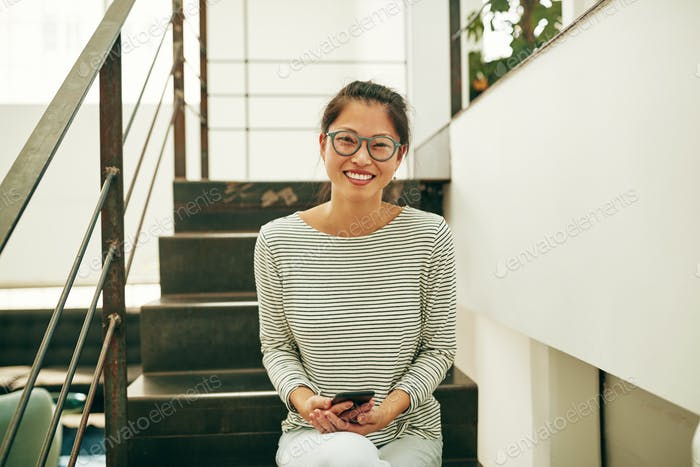 Smiling Asian businesswoman sitting on office stairs reading text messages