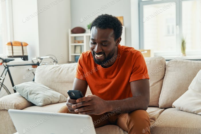 Carefree young African man using smart phone and smiling while spending time at home