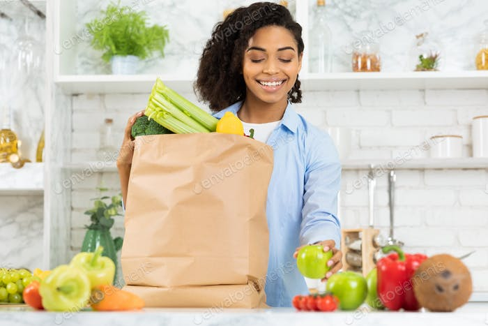 Satisfied black girl holding paper bag with food