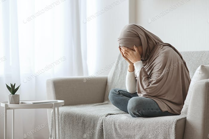 Depressed arabic girl in hijab crying on sofa at home
