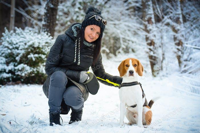Mujer joven hermosa se sienta con perro beagle en el bosque de invierno