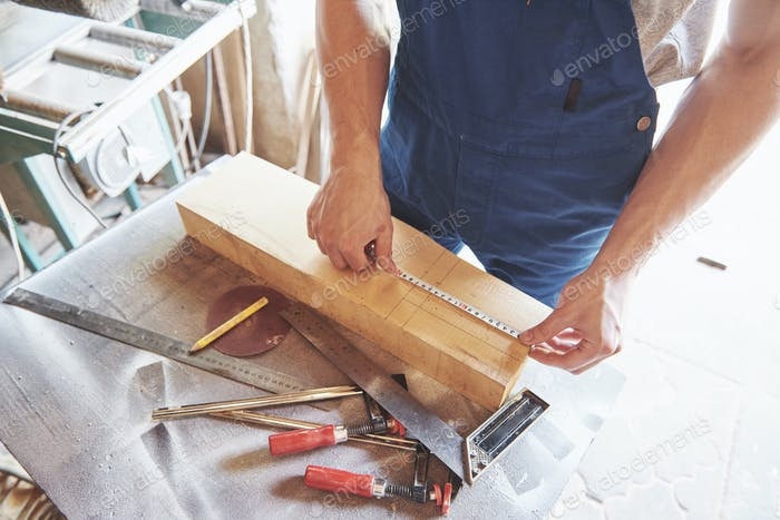 A man works in a joiner's shop, working with a tree