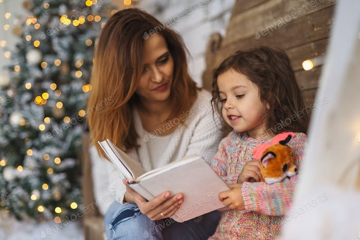 Mutter und Tochter lesen an Heiligabend