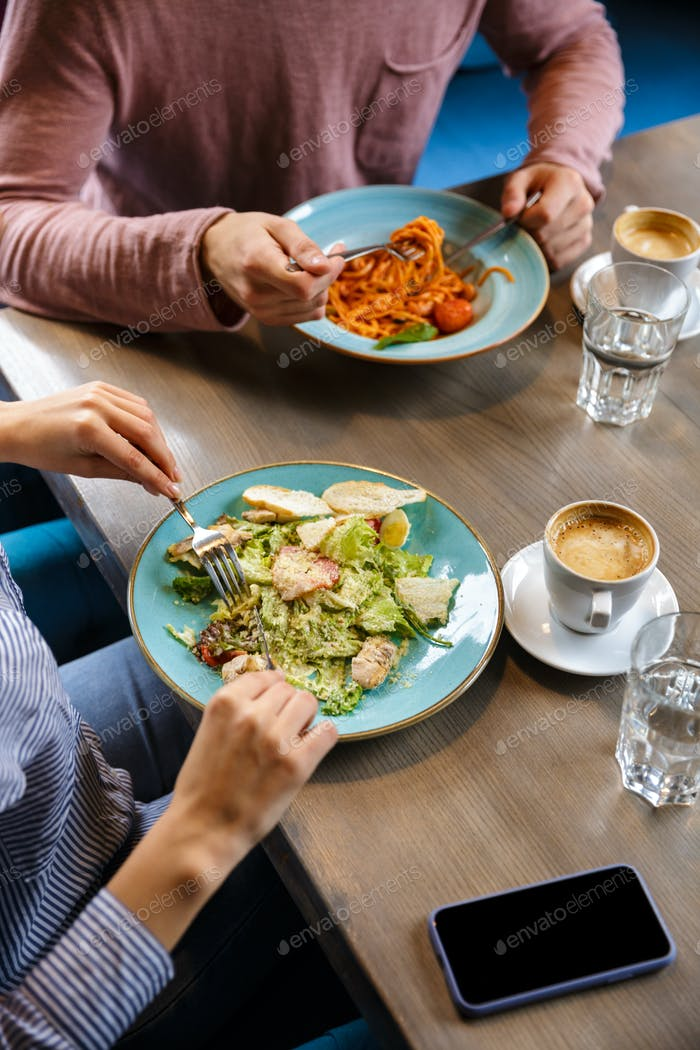 Nahaufnahme eines Paares mit Mittagessen über Café-Tisch