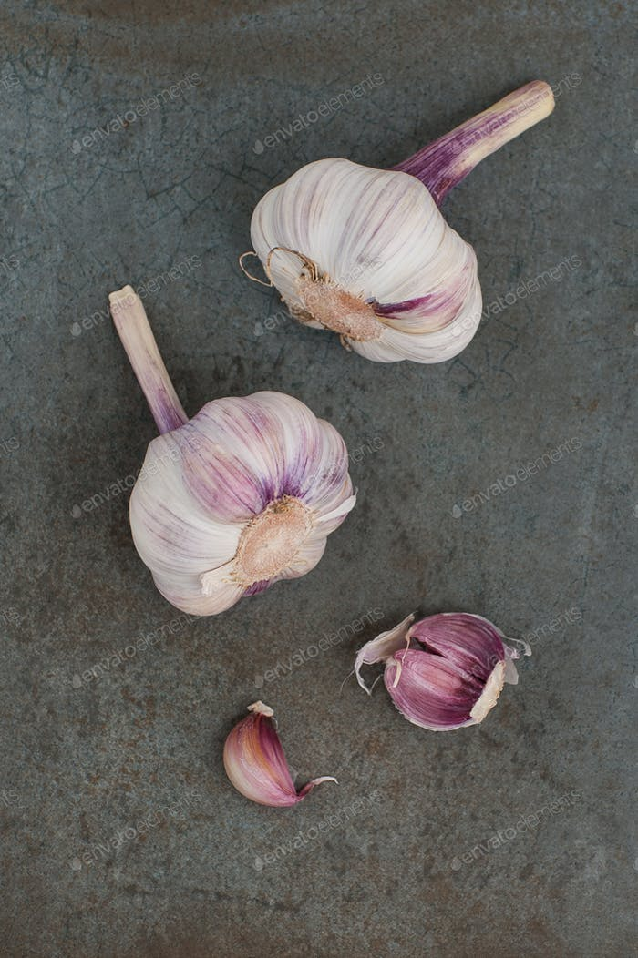 Two heads and cloves of garlic on a blue-gray stone background.