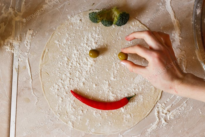 Dough basis for pizza in the shape of smile, on the table