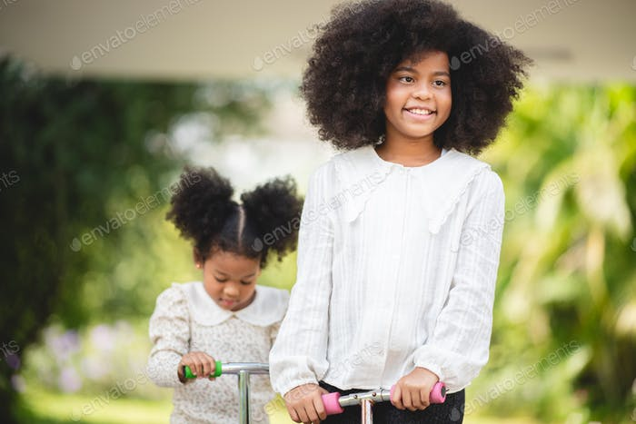 Two playful African sisters with curly hair enjoying and playing while riding scooter