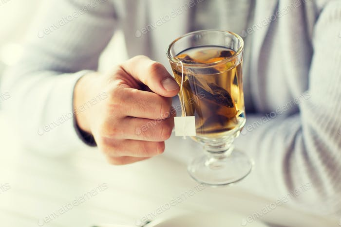 close up of man drinking tea at home or cafe