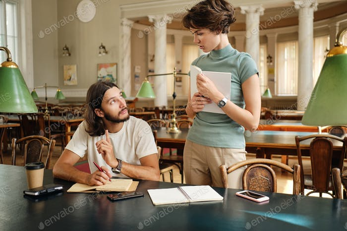 Attractive tutor girl discussing with student guy new topic during lesson in university library