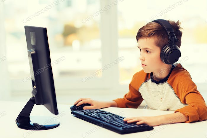 boy with computer and headphones at home