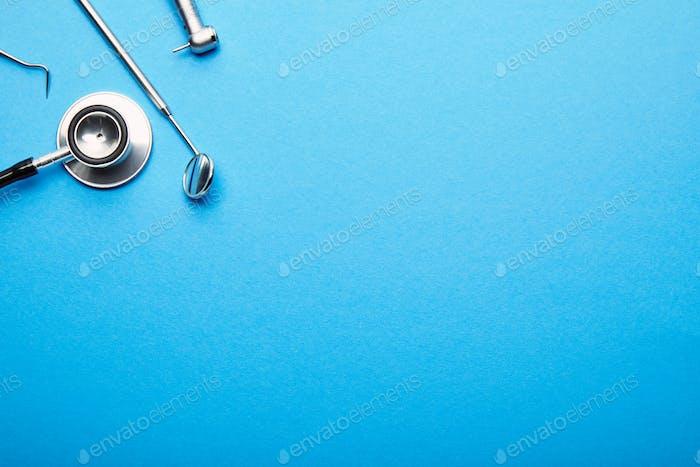 flache Lage mit angeordneten rostfreien Dentalinstrumenten auf blauer Tischplatte, Zahnmedizin und Zahnpflege