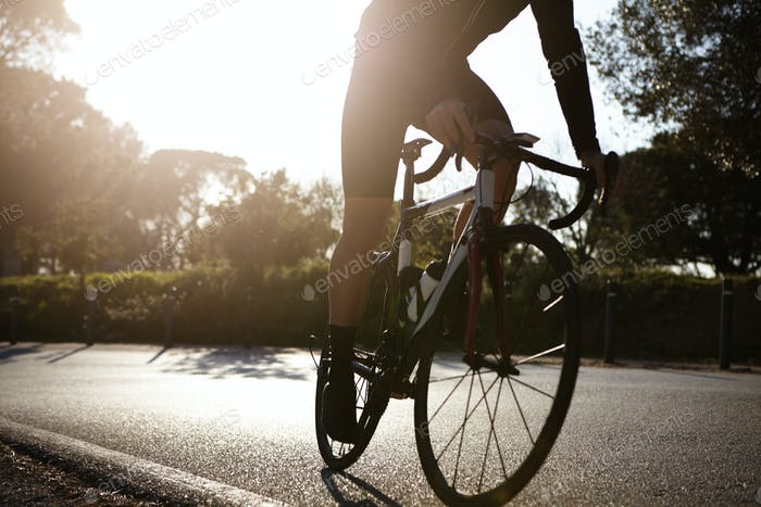 Cropped detailed shot of unrecognizable male wearing cycling clothing riding racing bike along aspha