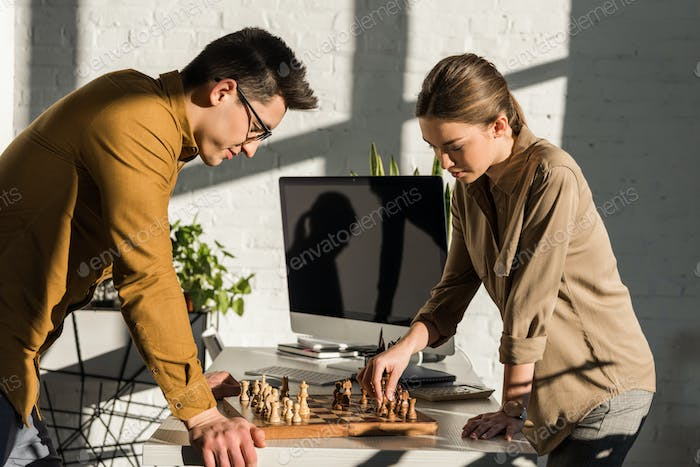 focused young colleagues playing chess at office