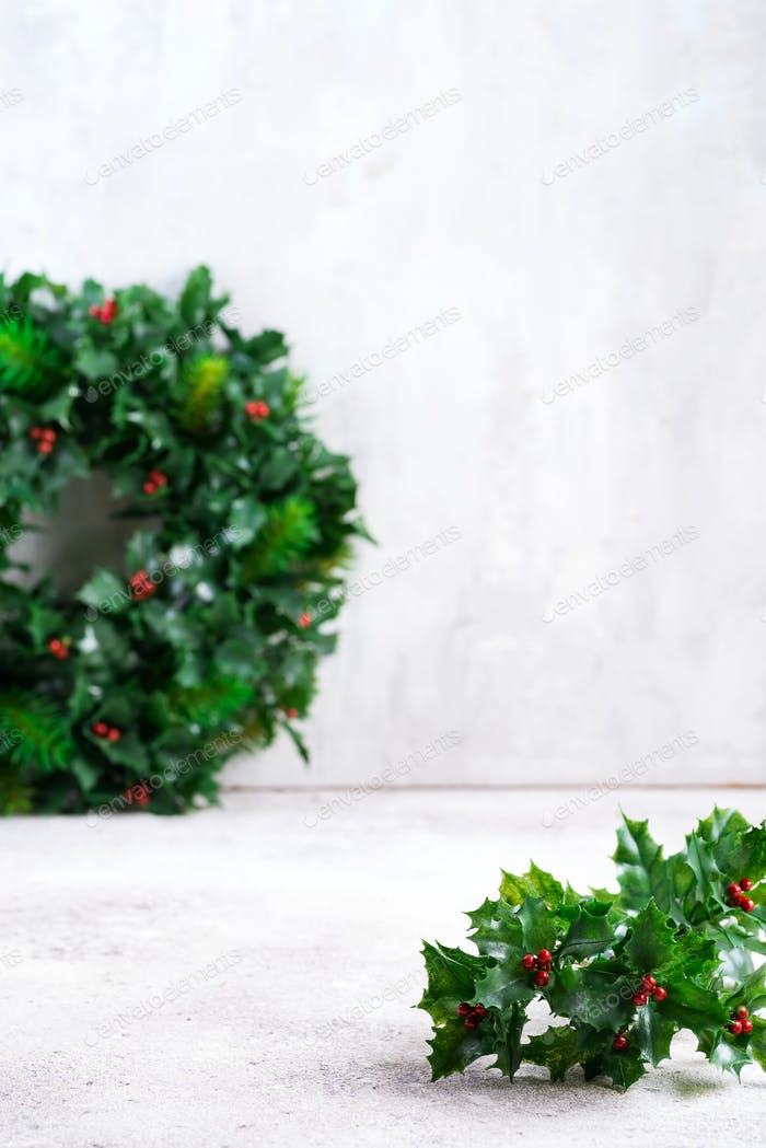 Simple Christmas background with holly, ilex leaves and tiny red fruits on stone background. Place