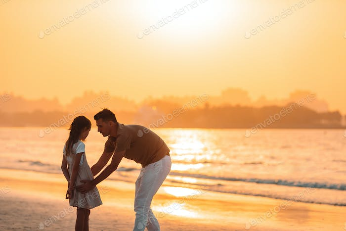 Beautiful father and daughter at the beach enjoying summer vacation