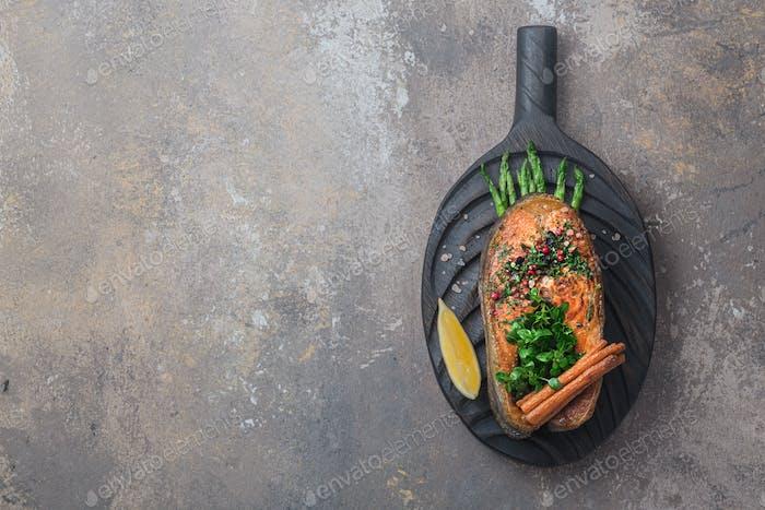 Gebratenes Lachssteak mit Gemüse auf Holzbrett, flacher Kopierraum