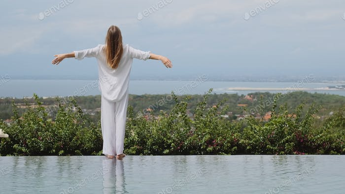 Back view of girl in sleepwear standing at the edge of swimming pool on villa with amazing view