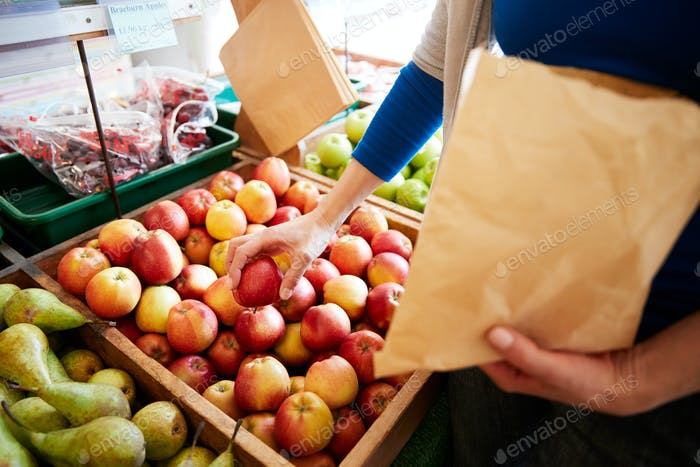 Nahaufnahme der frau kunde mit papiertasche kaufen frische äpfel in bio-farm shop