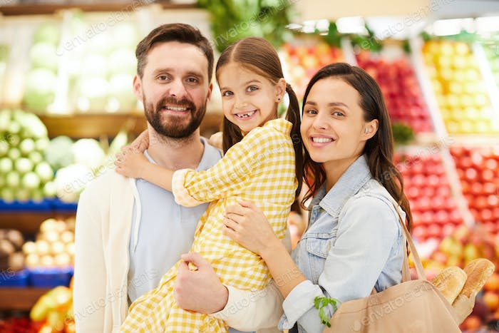 Cheerful friendly family embracing in food store