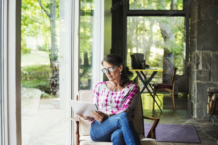 A woman seated by a window holding a digital tablet.