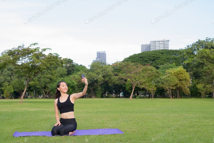 Woman Taking Selfie With Mobile Phone While Sitting On Yoga Mat In Park