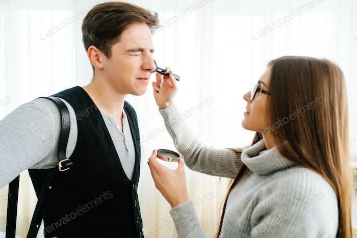 Woman doing makeup guy