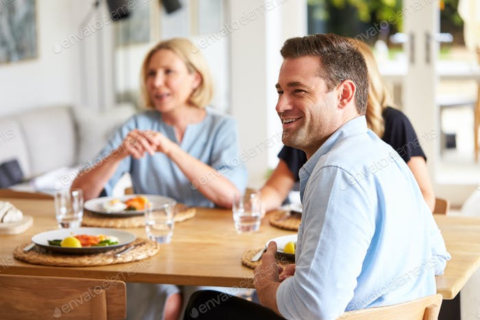 Family With Senior Mother And Adult Offspring Eating Brunch Around Table At Home Together
