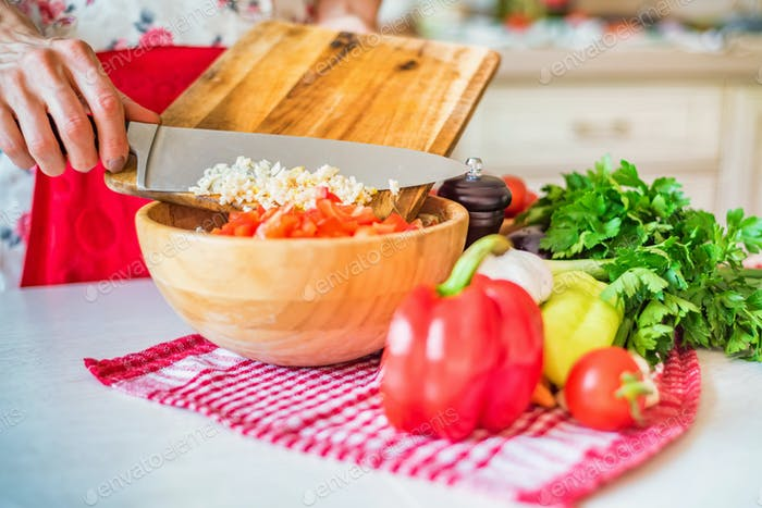 Female hand put chopped garlic in wooden bowl with salad in kitchen. Cooking vegetables