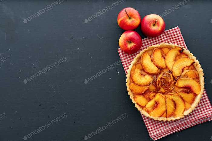 Apple tart pie and red apples on wooden table