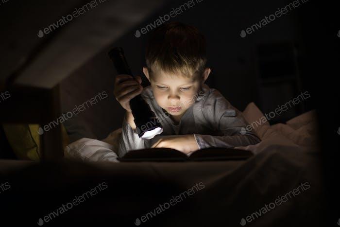 Cute Little Boy Lesung mit Taschenlampe