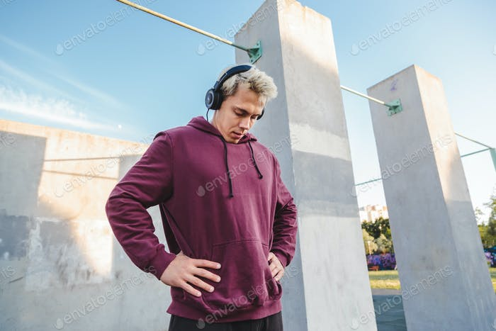 Sportsman warms up, doing neck rotation exercises and listening to music in headphones