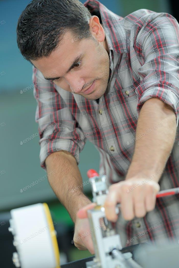 hübscher Handwerker arbeiten mit Elektrohobel in der Werkstatt