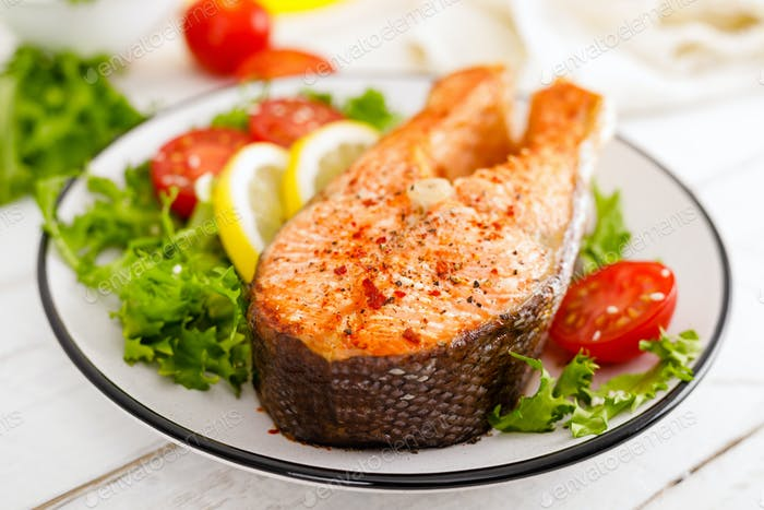 Salmon fish steak grilled and fresh vegetable salad with tomato and lettuce. Healthy food. Top view