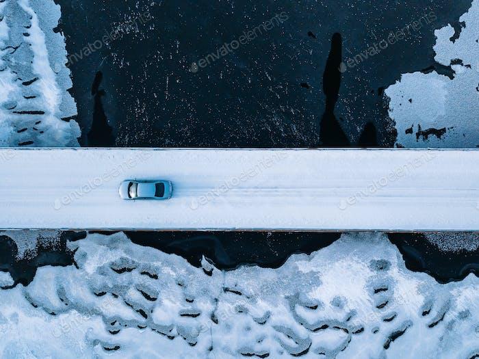 Aerial top view of bridge road above frozen river in snow winter Finland.