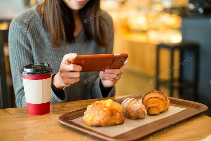 Frau fotografiert auf Bäckerei im Café