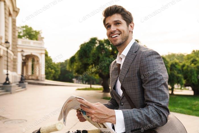 Happy cheery business man holding newspaper