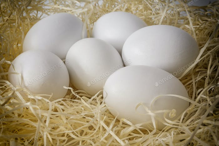 Close-up white chicken eggs on a bed of straw