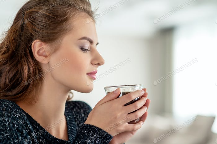 Beautiful woman drinks coffee and enjoying the taste