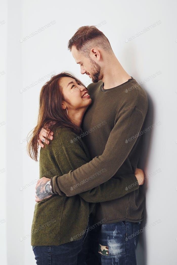 Счастливая многоэтническая пара в помещении в студии