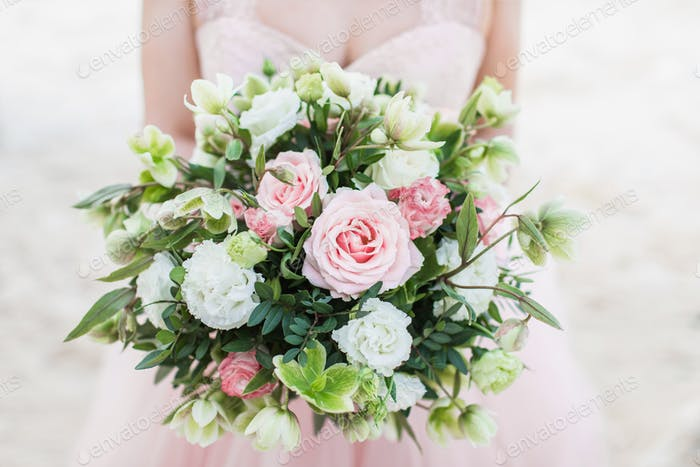 Beautiful wedding bouquet in woman hands, pink rose, tulips, carnation, greens. Light pastel color.