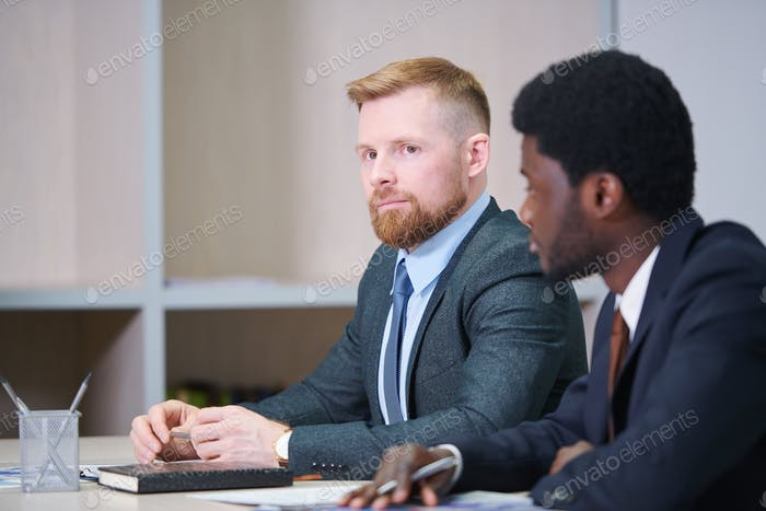 Serious young businessman listening to speaker at seminar