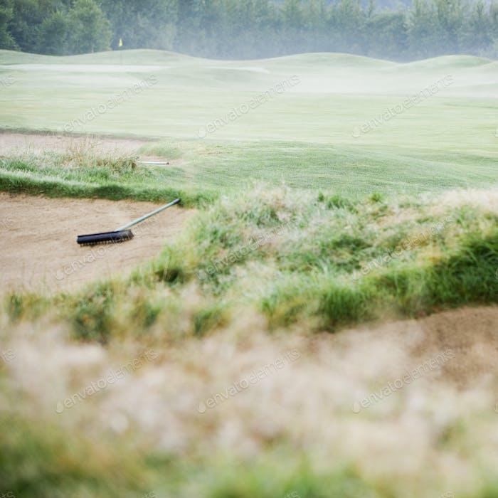 Rake in sand bunker on misty golf course.