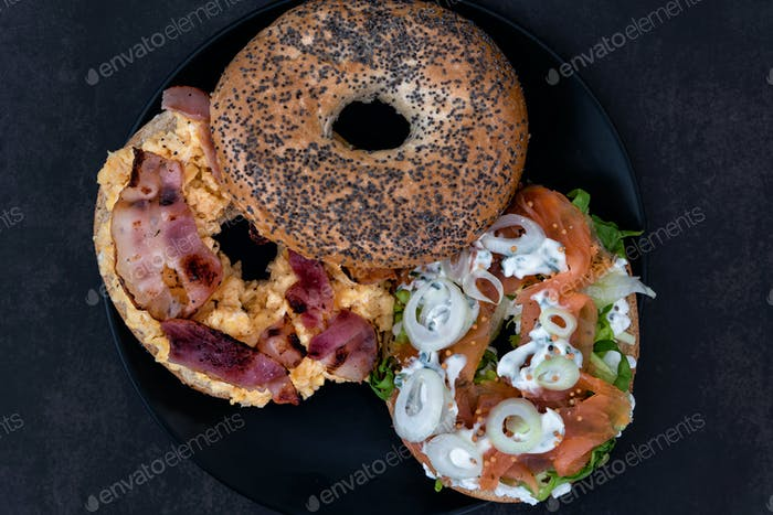 Two different bagels with lox and bacon on a black plate in dark setting
