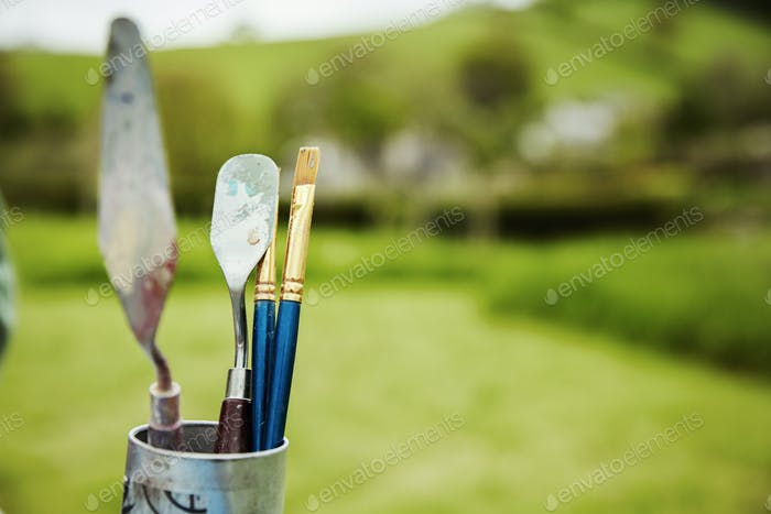 A tin with a selection of artist's tools, paintbrush and palette knives, outdoors.