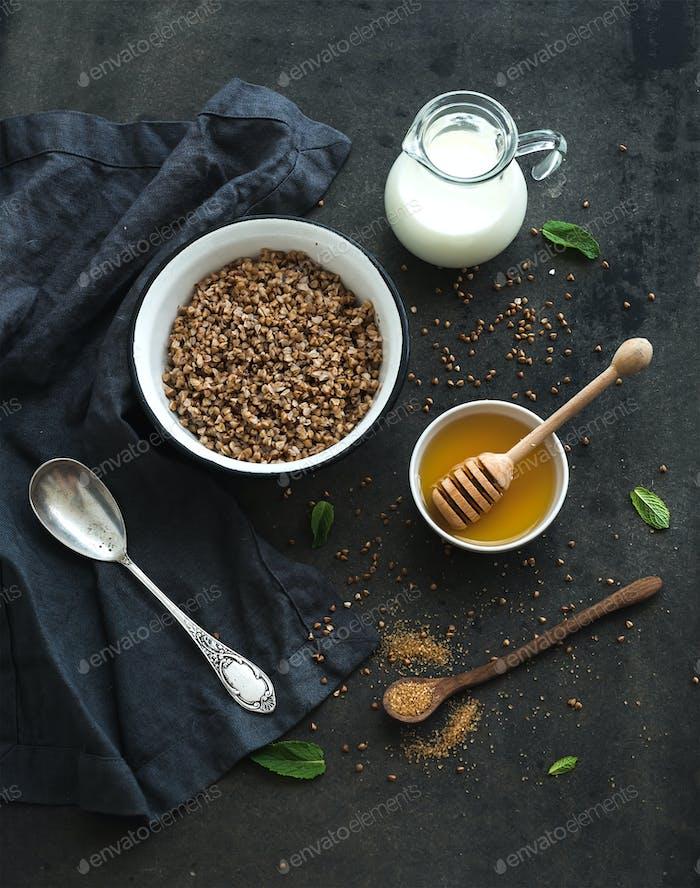 Rustikales, gesundes Frühstücksset. Gekochte Buchweizengrütze mit Milch und Honig auf dunklem Grunge-Hintergrund