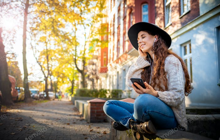 Beautiful stylish woman sitting on street with crossed legs at autumn day and using mobile phone